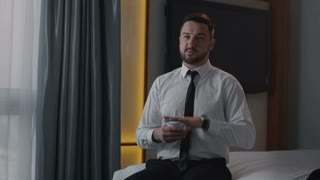Elegant bearded man in formal outfit sitting on bed in hotel and learning speech making marks in keynotes.