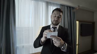 Elegant bearded man in suit standing in front of mirror in hotel room and rehearsing public speech holding pile of papers.