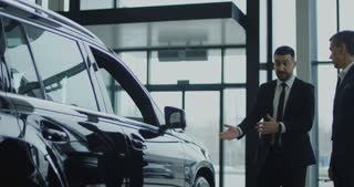 Elegant salesman inviting potential buyer to get in the car in showroom. Slow motion. Shot on Red cinema camera