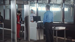 Employees checking passengers at counter with gates passing border control at airport.