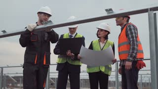 Engineer explain to workers how to mount solar panels on unfinished constructions on solar farm