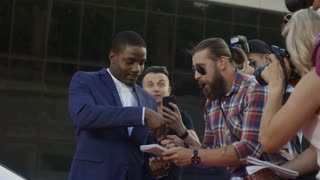 Ethnic celebrity man giving autographs to people on red carpet and makes photos