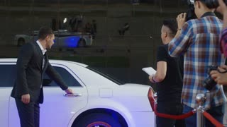 Ethnic celebrity man walking out of limousine and giving autographs to people on red carpet