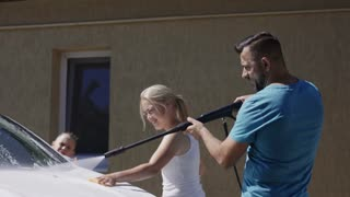 Excited couple with children spraying white car with soap and washing it while having fun all together
