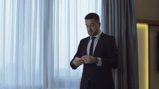 Expressive man in formal suit walking in hotel room with paper notes and training public speech expressively near window.