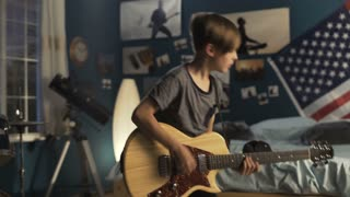 Expressive teen boy learning guitar play while standing in bedroom and playing with passion
