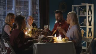 Family clinking with glasses and starting to eat while sitting at table with candles on Thanksgiving day