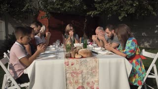 Family sitting at table outside and praying together during the reunion