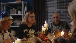 Family with children and grandparents gathering at table at home having holiday feast on Christmas holiday enjoying evening together