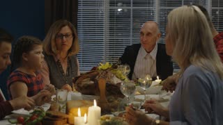 Family with children and grandparents gathering at table with candles and plenty of delicious food celebrating traditional Thanksgiving day