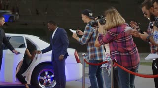 Famous African-American man and woman walking out of limo and posing for shoots and giving autographs on red carpet of celebrity event