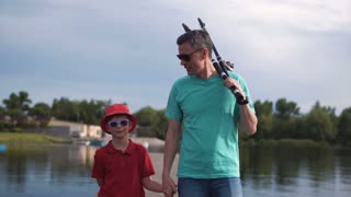 Father and his young son fishing in the evening at a tranquil lake walking along the jetty hand in hand carrying their rods and smiling happily