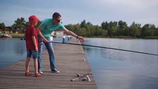 Father and son fishing off a wooden jetty with rods and reels in evening light in a concept of quality time and healthy outdoor lifestyles