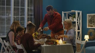 Father of family with children and parents at table carving roasted turkey while celebrating Thanksgiving day at home