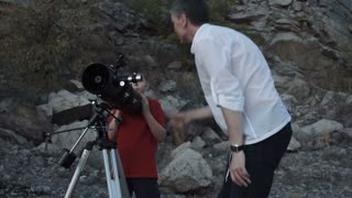Father sets up telescope for explore stars with son on rocky shore