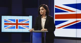Female news anchor presenting British news pointing and gesturing with her hand as she speaks standing behind a small podium. 4K shot on Red cinema camera
