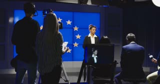 Female news anchor reading the news in front of a European flag with a production team and camera man in the studio