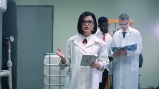 Female scientist in glasses and white lab coat holding tablet and walking through lab towards camera while talking and pointing to productional equipment