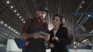 Flight mechanic checking something on a tablet-pc with a smartly dressed young woman standing inside an aircraft hangar