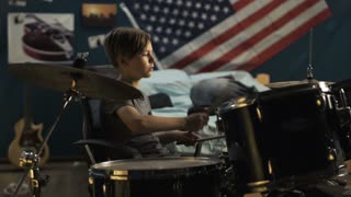Focused teen sitting in chair and playing drums with drumsticks in modern bedroom at home