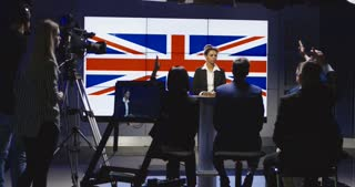 Formal African-American woman as official representative of Great Britain holding speech on press conference against screen with country flag. 4K shot on Red cinema camera