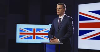 Formal businessman in suit standing on stage against screen with Great Britain flag and giving speech for auditorium in studio. 4K shot on Red cinema camera