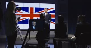 Formal businessman in suit standing on stage against screen with Great Britain flag and giving speech for auditorium in studio. Slow motion. 4K shot on Red cinema camera