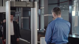 Formal man walking through gates in airport leaving metal things on conveyor by request of security.