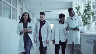 Four diverse young students in white coats walking in medical school hall, holding copybooks and talking. Front view stabilized 4K shot
