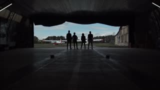 Four people standing in an aircraft hangar silhouetted against the sky watching two small aircraft outside in a low angle view