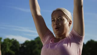 From below view of serious blond woman doing exercise for shoulder muscles with metal dumbbells standing outside in sunlight