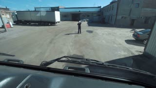 Front view from cabin of the truck of the manager leading the truck arrival to the warehouse