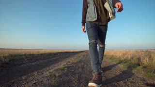 Front view of unknown lone man walking away down a rural road in a low angle view in a conceptual motion clip