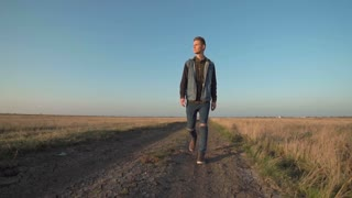 Front view of young lone man walking away down a rural road in a low angle view in a conceptual motion clip