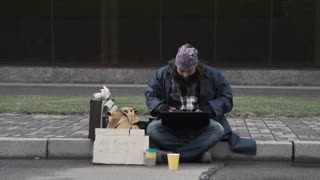 Funny homeless beggar using a laptop while receiving a good news as a surprising inheritance or winning a fortune after betting online