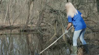Girl in t-shirt of volunteer company cleaning up trash on pond with rake and talking to black mug managing process.