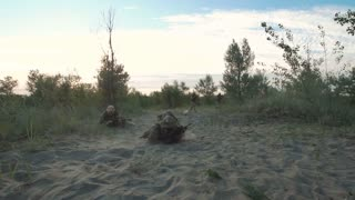 Group of armed military men crawling on sand together near explosions on field in smoke