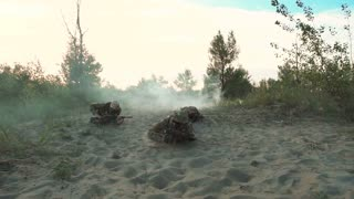 Group of armed military men crawling together near explosions on field in smoke