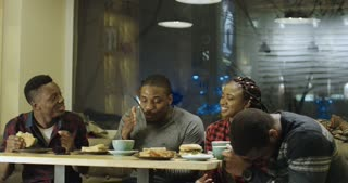Group of cheerful African-American people listening to young man telling story expressively while chilling in cafeteria.