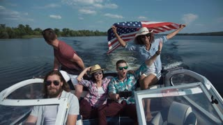 Group of diverse cheerful friends on boat celebrating Independence day and having fun