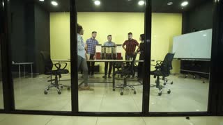 Group of diverse co-workers discussing by miniature of building in modern office