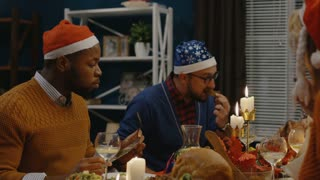 Group of diverse friends gathering at table together and celebrating Christmas with delicious meal and candles on table