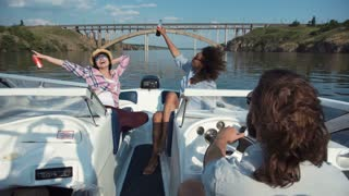 Group of diverse happy women relaxing on board a motor boat as they approach a bridge along a river laughing and cheering waving their beers in the air
