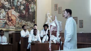 Group of diverse young interns or medical students at an anatomy exam. Doctor asking to african student raised hand, to demonstrate the structure of the human skeleton and circulatory system