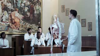 Group of diverse young interns or medical students at an anatomy lecture with a doctor demonstrating the structure of the human skeleton and circulatory system. Student asking question