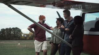 Group of diversity young people talking next to small airplane outdoors