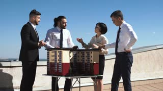 Group of engineers and architects in a meeting standing outdoors on a pation discussing a model of office or apartment blocks in a low angle view against blue sky