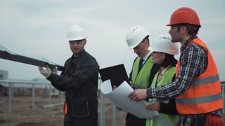 Group of engineers or technicians on a solar farm standing between constructions for mounting the photovoltaic panels discussing a blueprint in a management concept of renewable energy and electricity