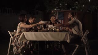 Group of friends dining and sitting together at the table in backyard and talking about something