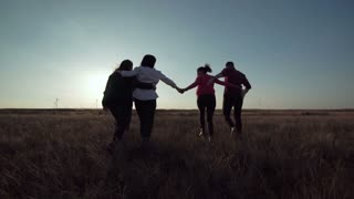 Group of friends running through field towards wind farm at sunset